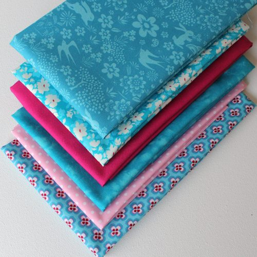 Fat quarter fabrics in peacock blue and pink.