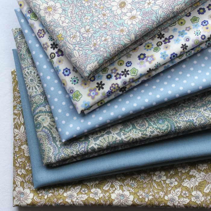 bundle of floral fabrics cut in fat quarters