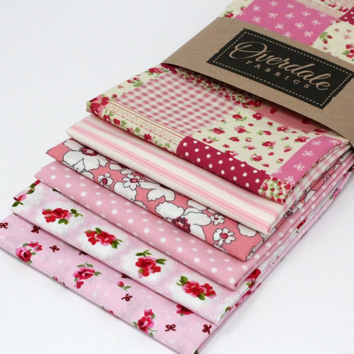 A collections of pink fat quarters with a vintage theme.
