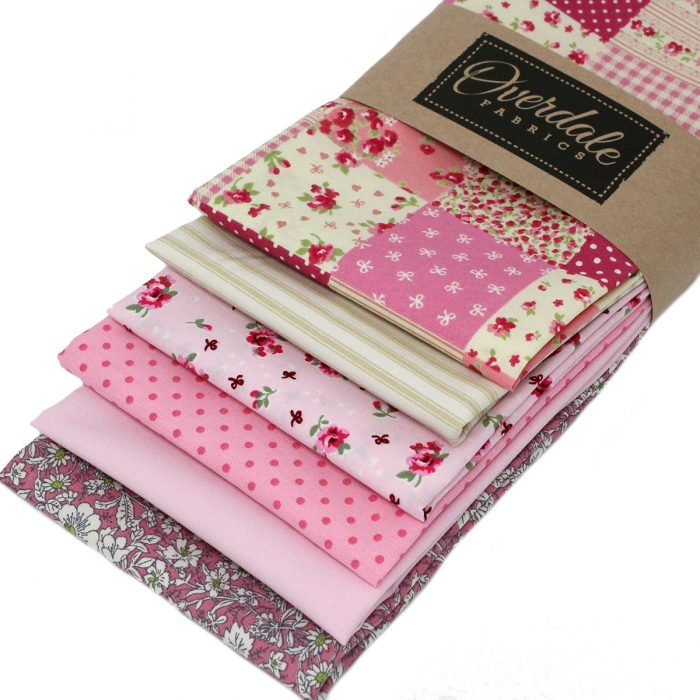 A pack of pink fat quarter fabrics with a vintage look.