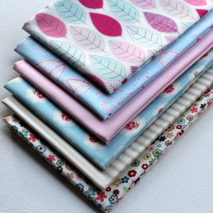 A pack of six fat quarter fabrics in pastel colours.