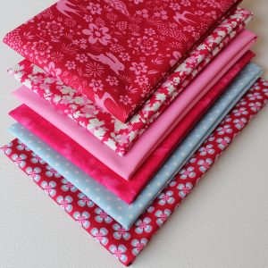 A collection of fat quarter fabrics with a country theme in shades of pink.