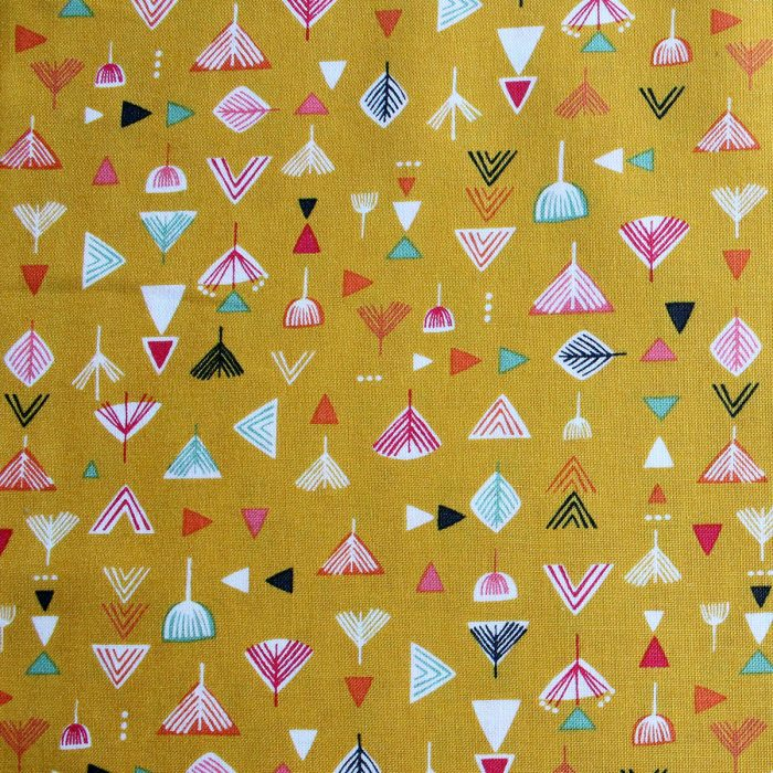 Mustard coloured fabric featuring arrow head designs.