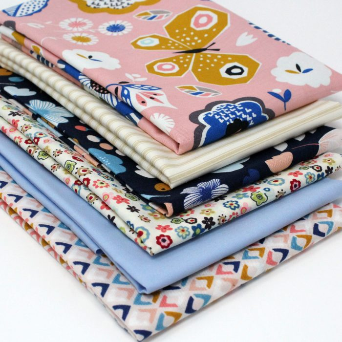 A collection of fabrics with floral and butterfly designs in pinks and blues.