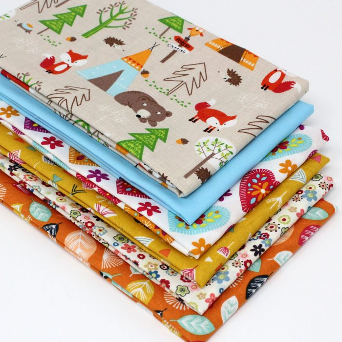 Woodland creatures in a camping scene with coordinating fat quarter fabrics.