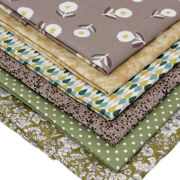 Fat quarter fabrics in shades of green and tan.