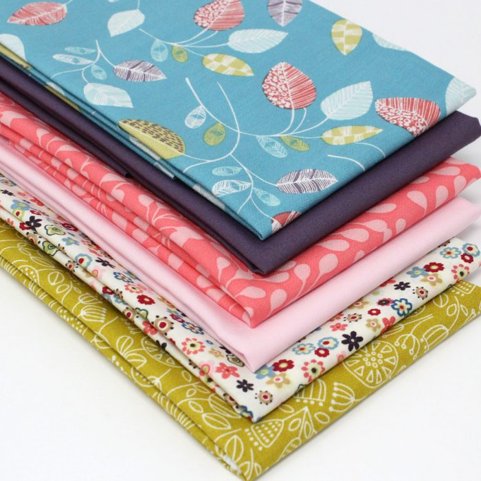 A collection of fat quarter fabrics in blues, greens and pinks with a natural theme.