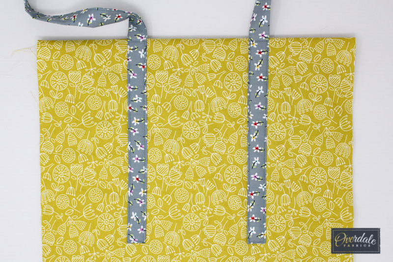 Attaching bag handles to a tote bag.