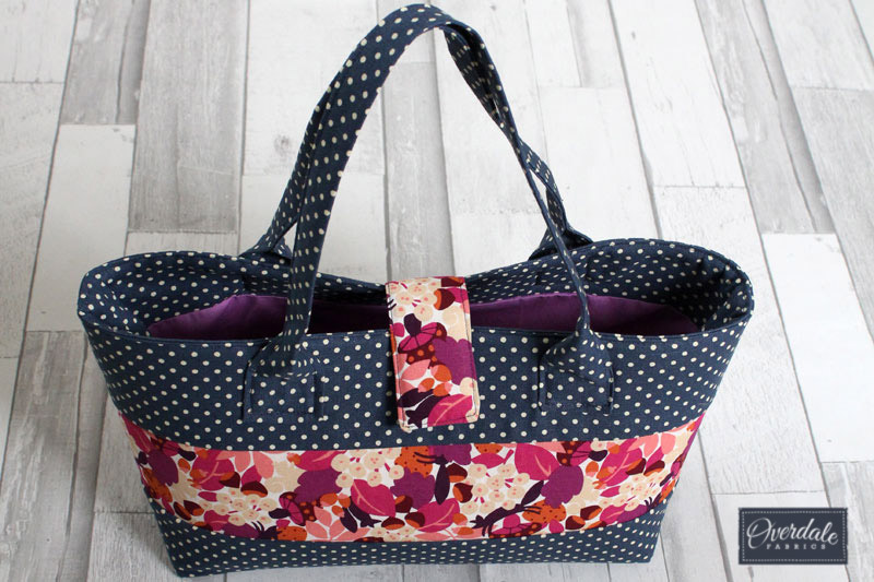 A patchwork handbag in pink and navy blue.