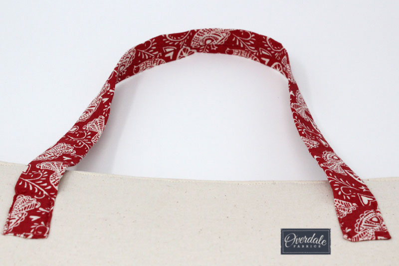Attaching bag handles to a Christmas handbag.