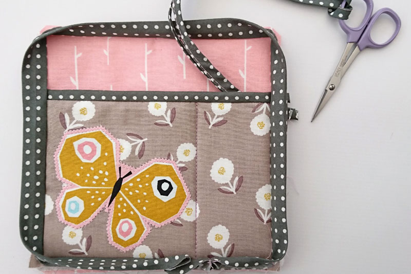 Detachable sewing caddy pocket decorated with a butterfly.