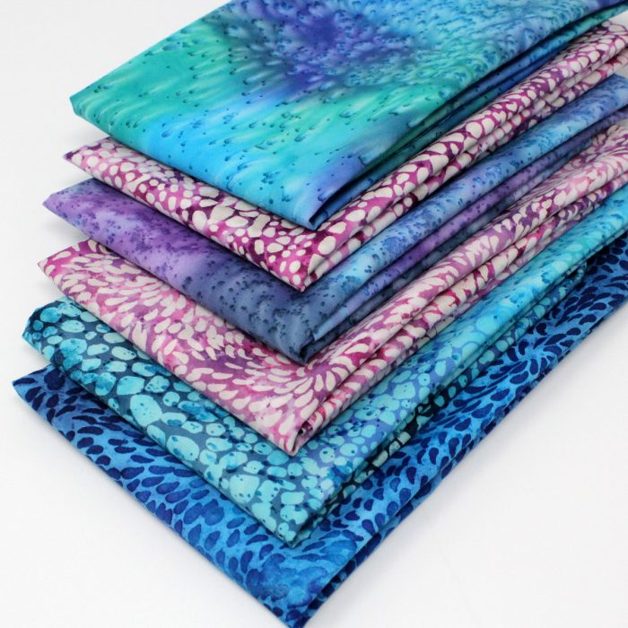 A set of batik fat quarters in pinks, blues and purples.