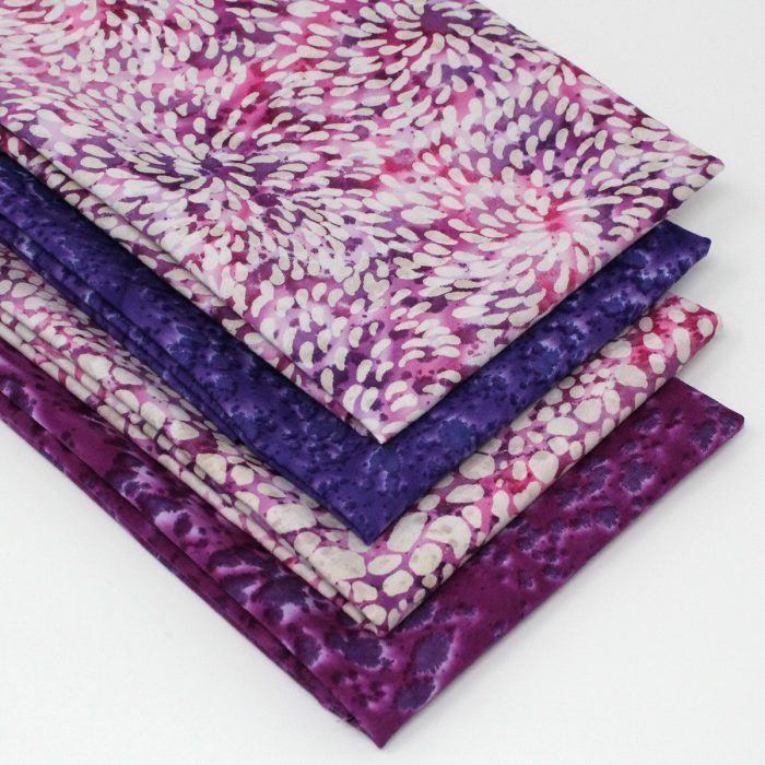A collection of batiks in purple and pink.