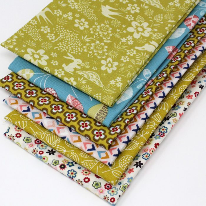 Fat quarter fabrics in sage green and teal blue.
