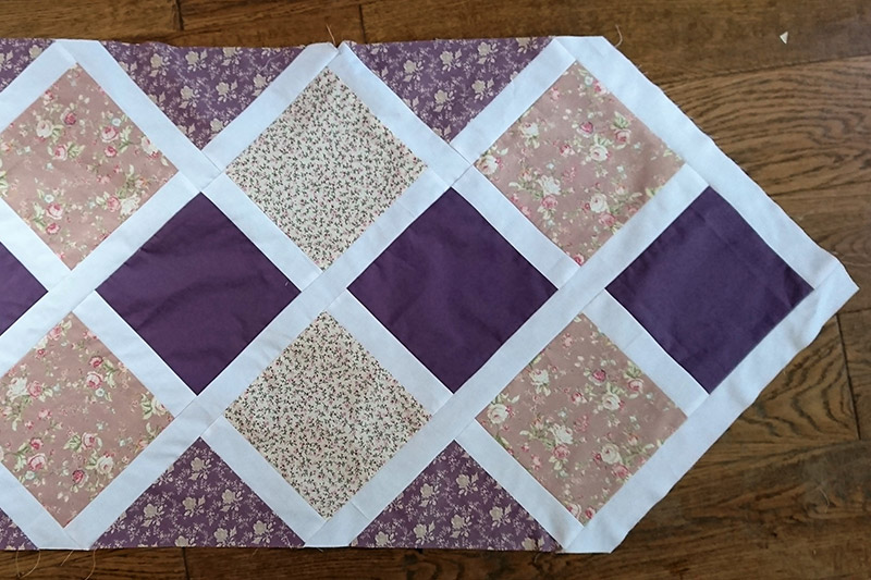 Diamond squares quilted together for a table runner.