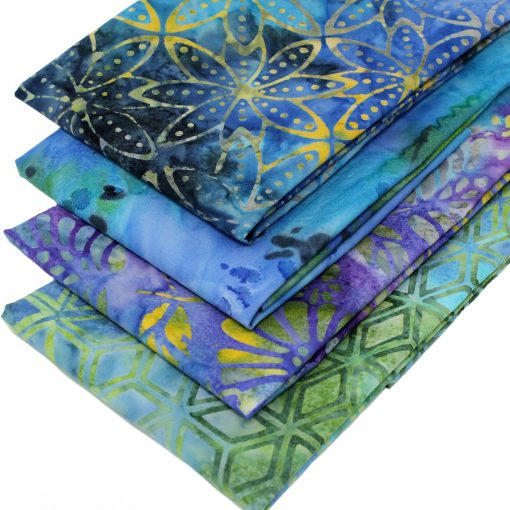 Blue, green and purple batik fabrics with floral designs.