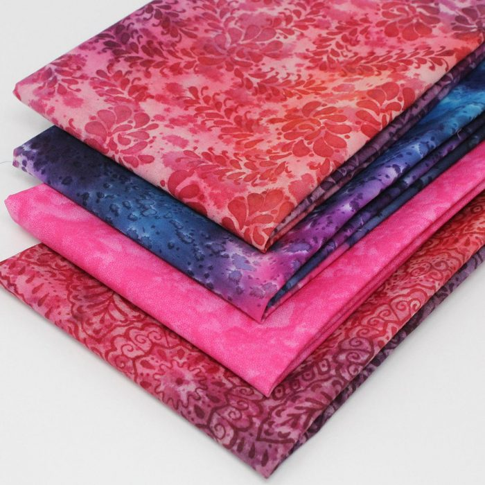 Four batik fat quarters in purple and red.