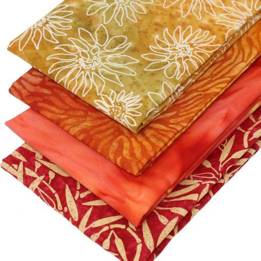Batik fabrics in shades of orange and yellow.