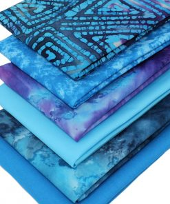 Blue and purple fat quarter fabrics including batiks and plain solids.