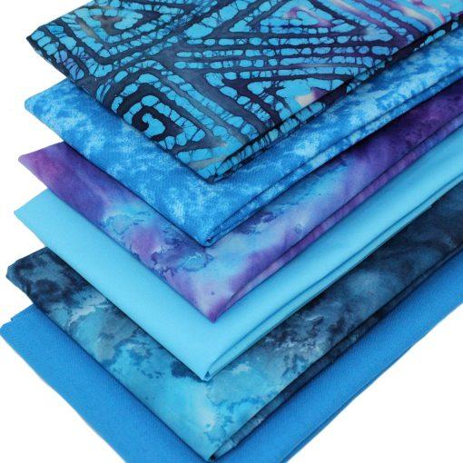 Blue and purple fat quarter fabrics including batiks and plain solids.