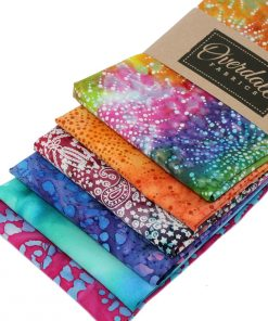 Batik fabrics in vibrant orange, pink, purple and green.
