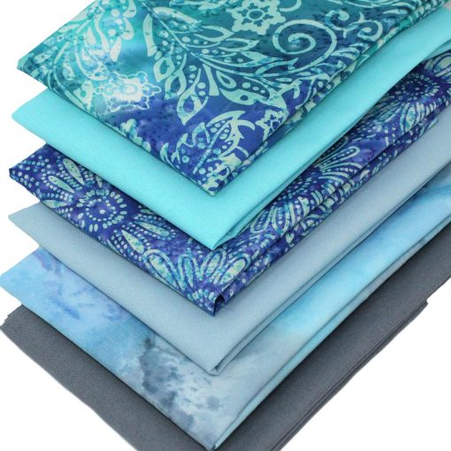 Batik and plain solid fat quarter fabrics in shades of blue and grey.