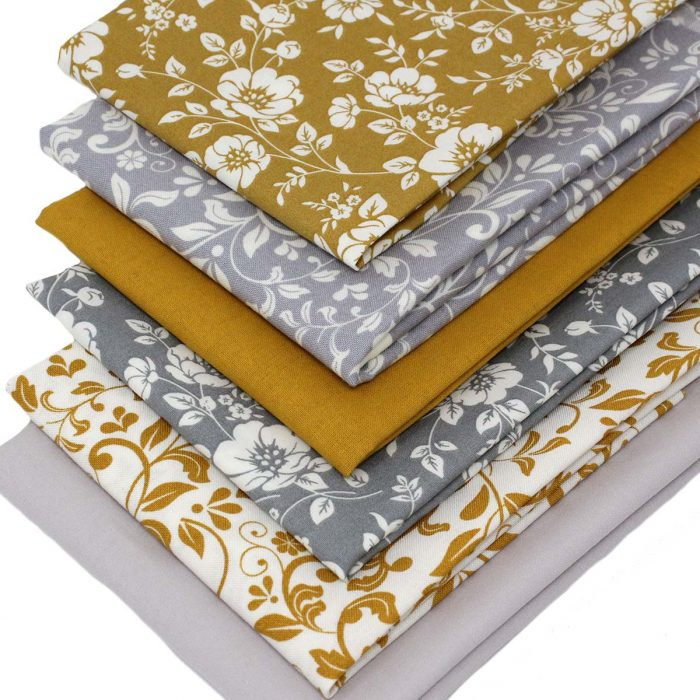 Floral and leaf fabrics in grey and mustard yellow.