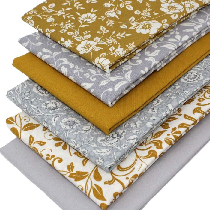 Fabrics in mustard yellow and grey with a floral theme.