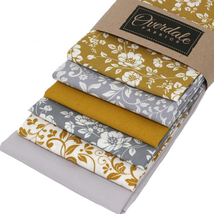 Yellow ochre and grey fat quarter fabrics with floral and leaf designs.