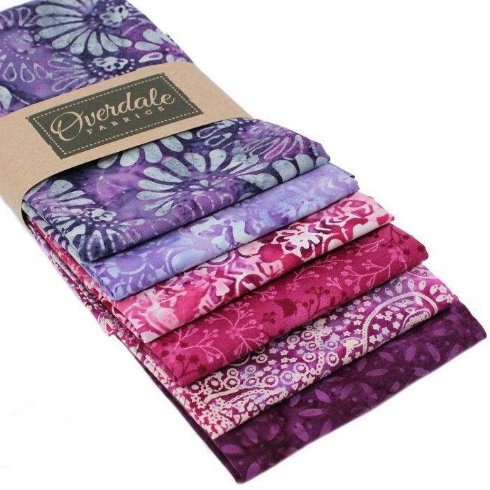 Batik fat quarters in purple and pink with a floral theme.