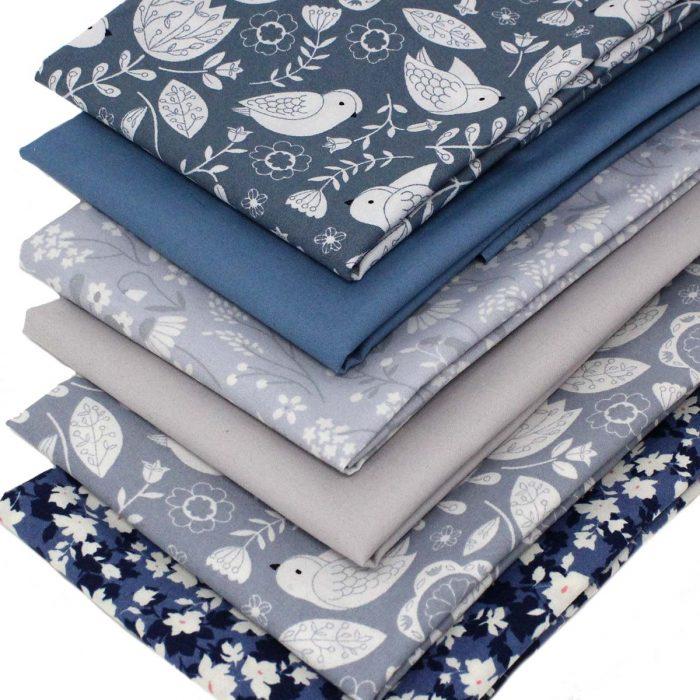 Slate blue and grey fat quarters with bird and flower prints.