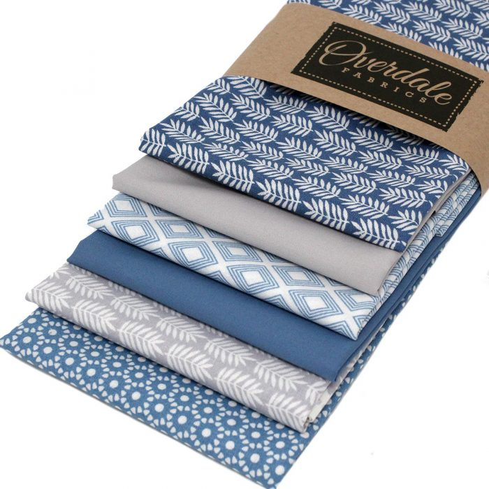 Printed grey and blue fabrics arranged as a set of six fat quarters.