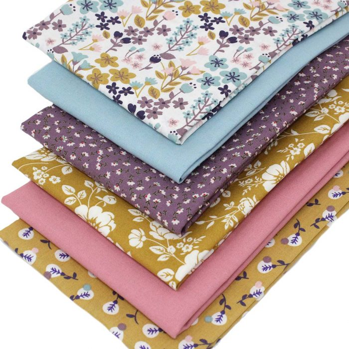 Fat quarter fabrics with flower designs in shades of ochre, pink and plumb.