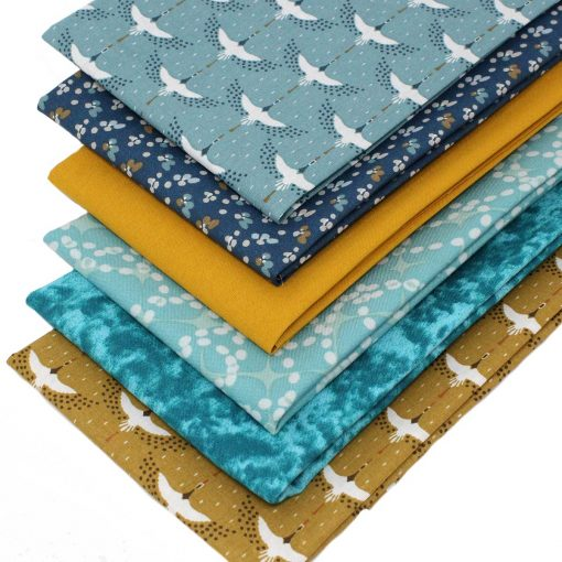 Fat quarter fabrics featuring cranes in ochre and blue.