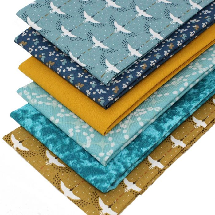 Fat quarter fabrics featuring cranes in ochre and blue.