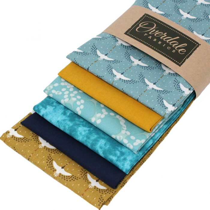 Fat quarter fabrics featuring cranes in blue and ochre.