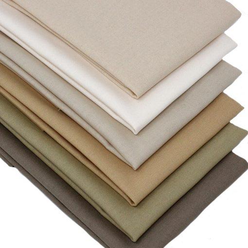 A set of fat quarter fabrics in natural shades.