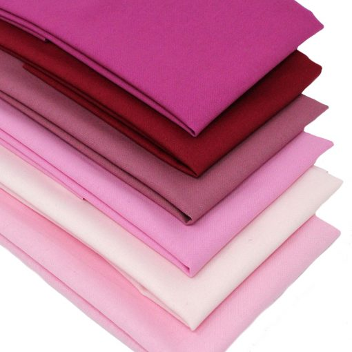 A set of fat quarter fabrics with colours ranging from soft pink to raspberry red.