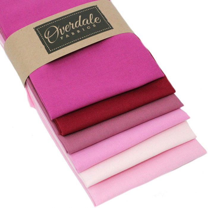 Plain solid fabrics in shades of pink and red.