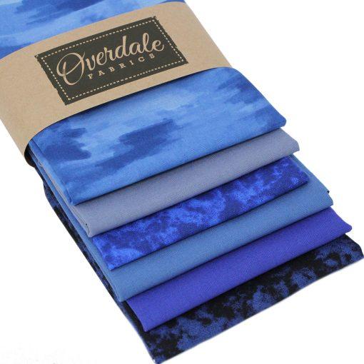 Rich blue fat quarter fabrics with dappled, mottled and plain designs.