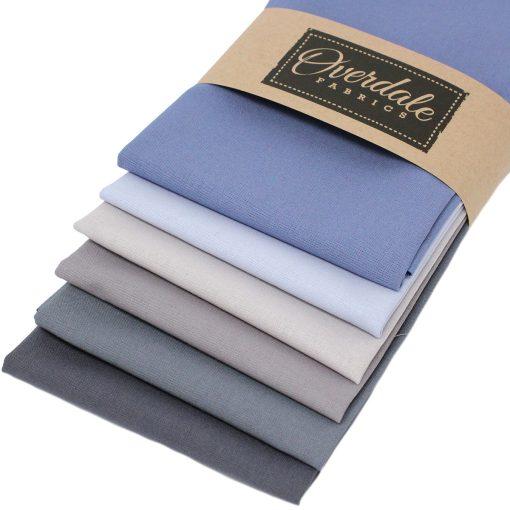 Fat quarter fabrics in graduating tones from blue to grey.
