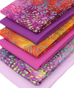Vibrant batik and plain solid fabrics with a pink colour theme.