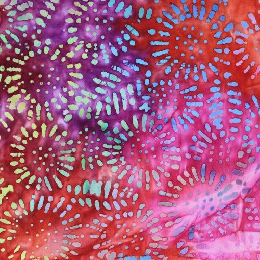 Pink batik fabric with a circular design.