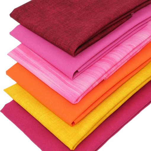 Vibrant fat quarter fabrics in red, pink, yellow and orange.