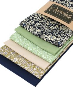 Fat quarter fabrics in green, blue and beige featuring flowers and plain solids.